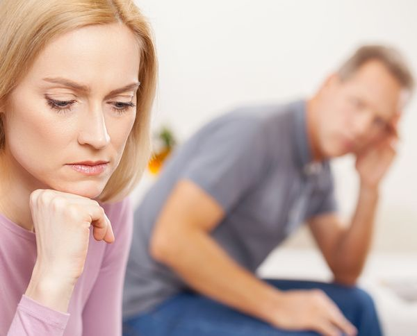 woman sitting on couch with husband upset